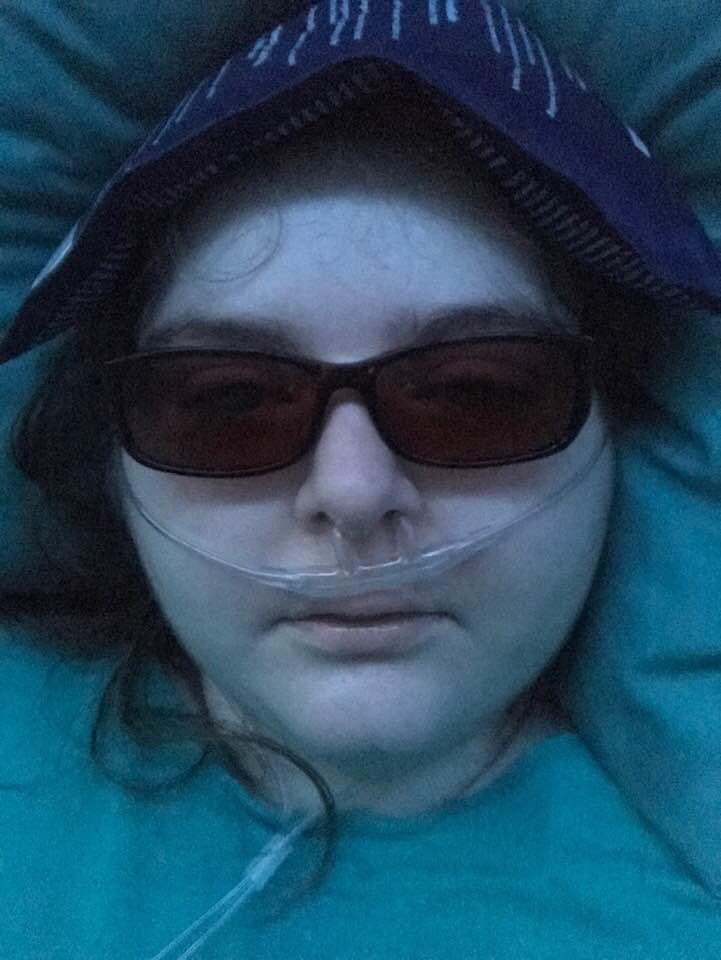 Kara wears dark glasses and has an ice pack on her head. She has an oxygen cannula in her nose. Her skin is pale and she looks very ill.