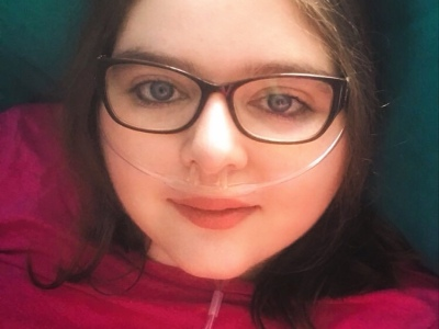 Kara Jane Spencer in a pink top. She wears glasses and has an oxygen nasal cannula