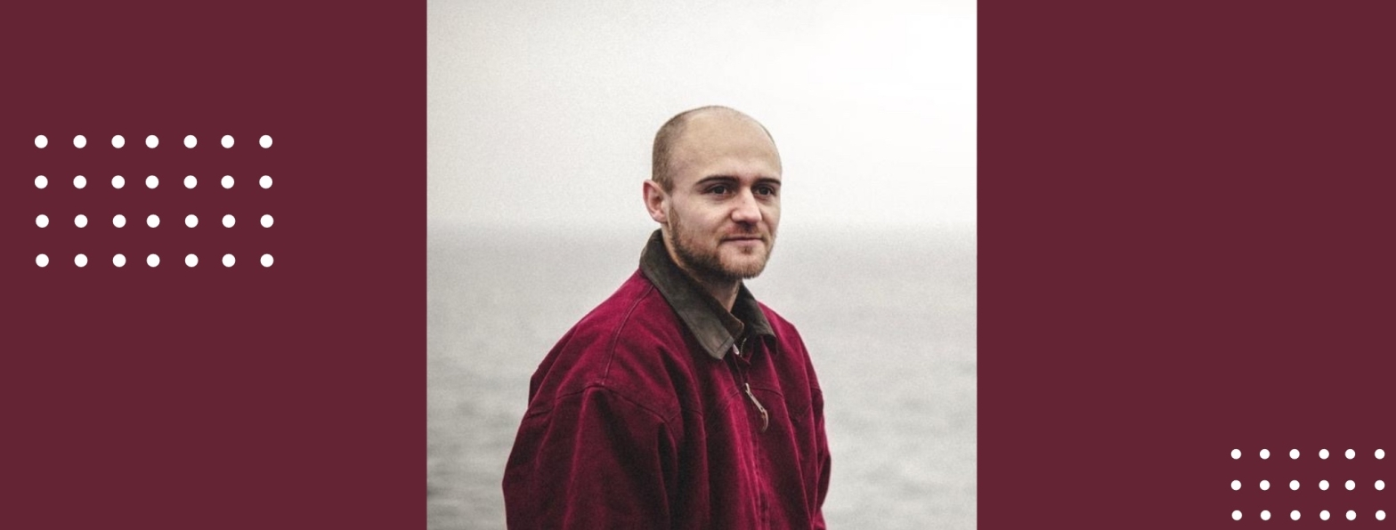 Liam Hicks looks slightly away from the camera. He is wearing a maroon jacket. A grey sea is behind him.